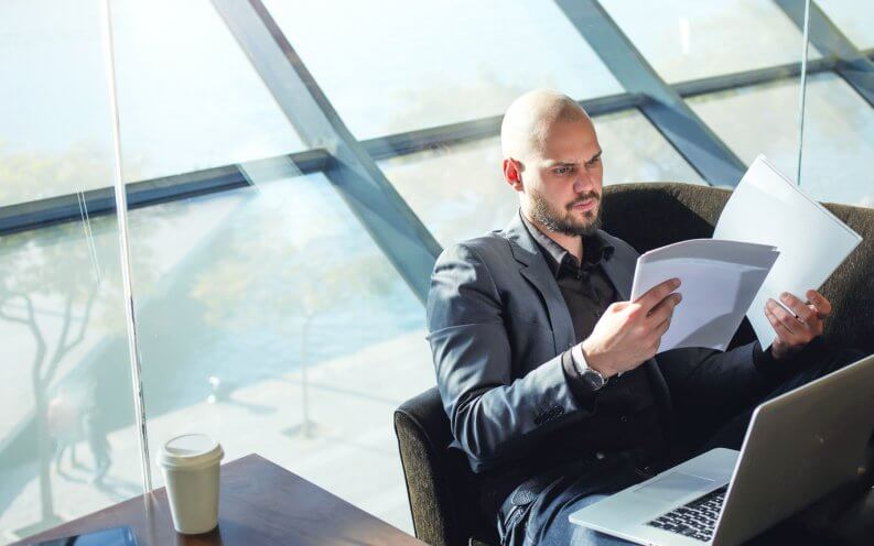 man looking at papers next to window
