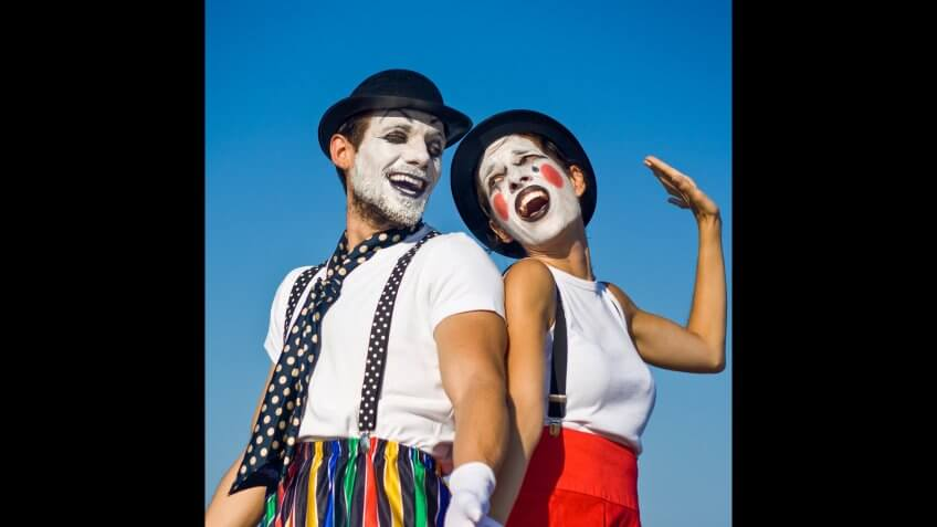 Two mimes standing against blue sky.