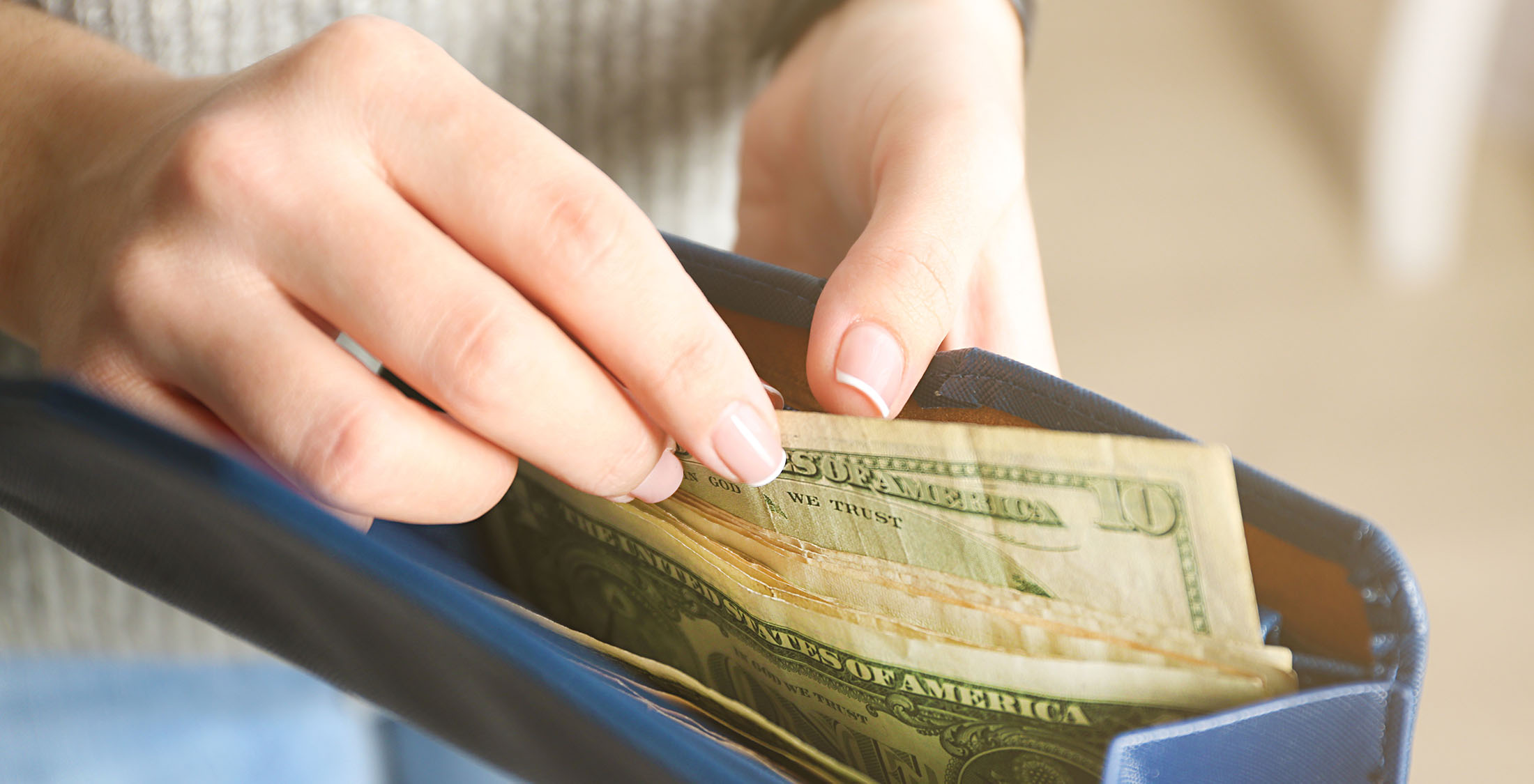 woman pulling money from clutch purse