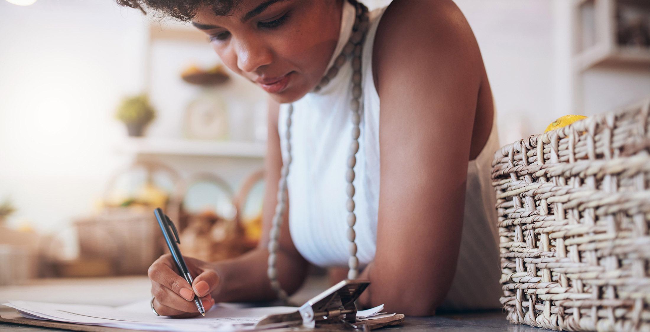 woman writing on clipboard