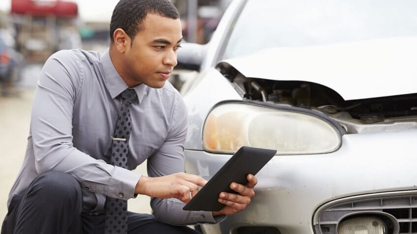 man checking broken car with tablet