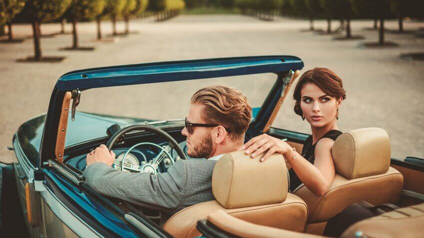 man and woman in luxury car