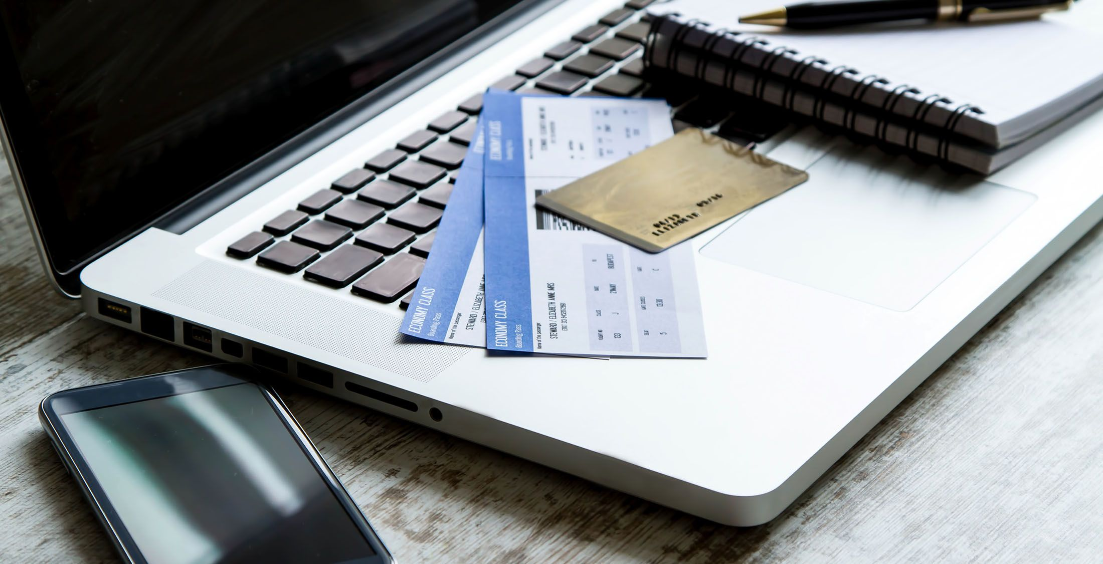 credit card and tickets on top of laptop