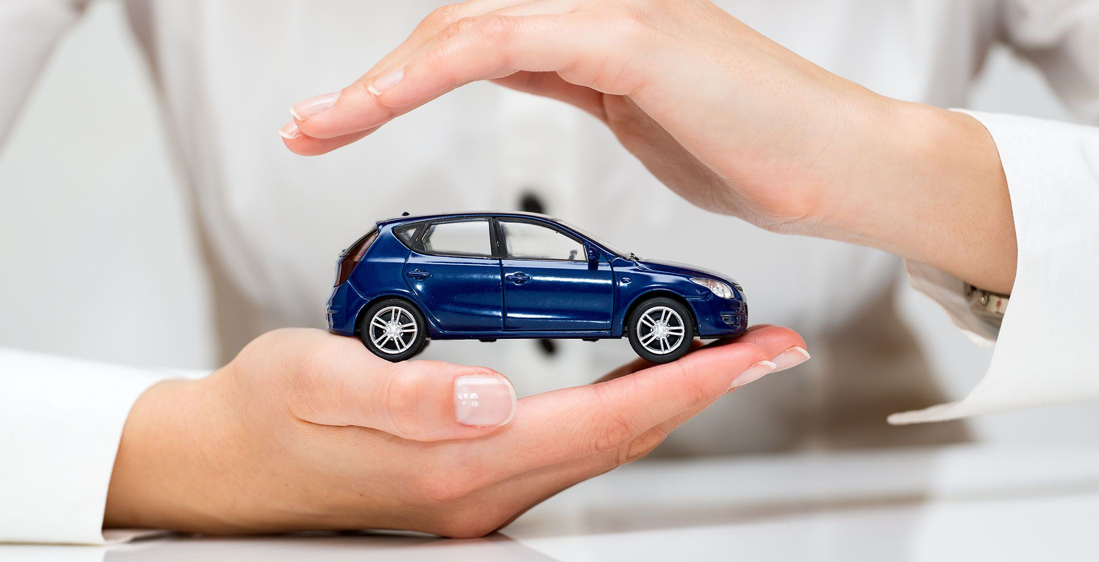 woman holding small car in hands