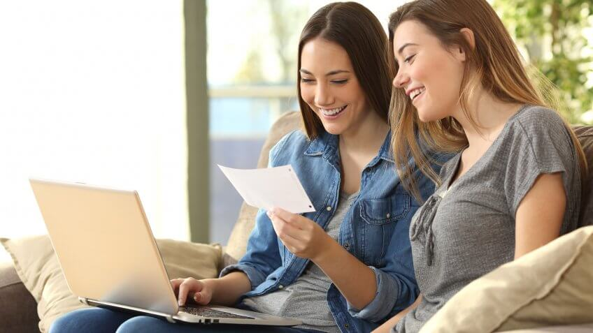two young women smiling looking at a piece of paper and laptop