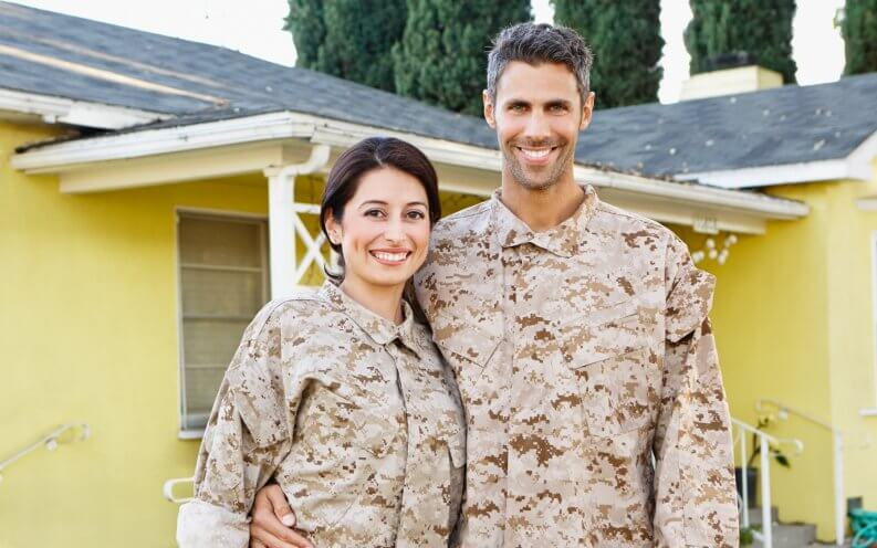 smiling veteran couple in front of yellow house