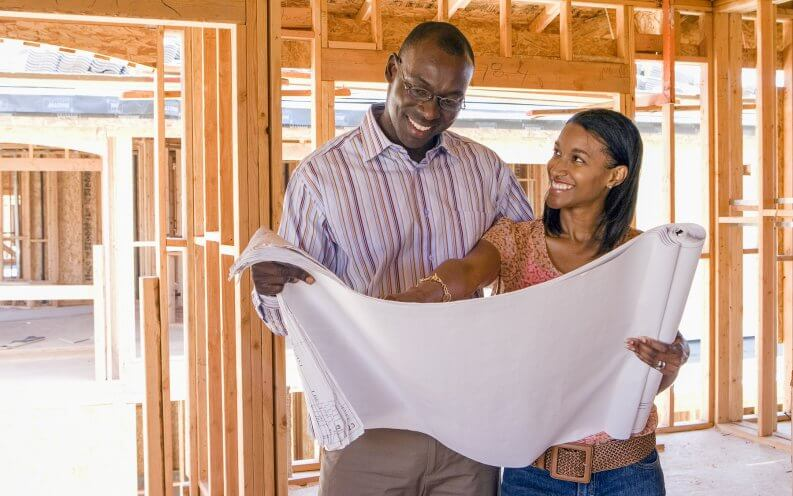 couple looking at blueprints of home