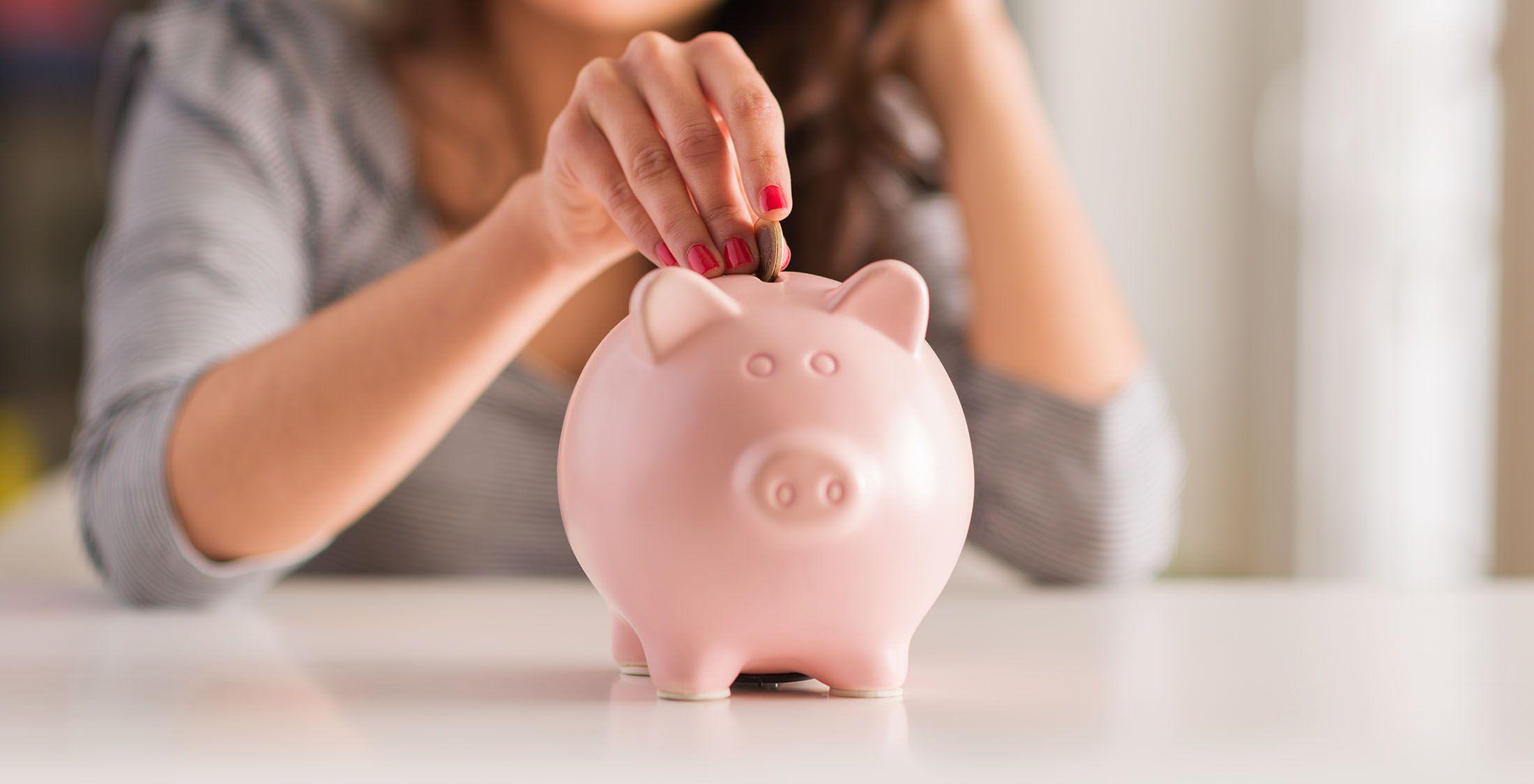 woman insert coin into piggy bank