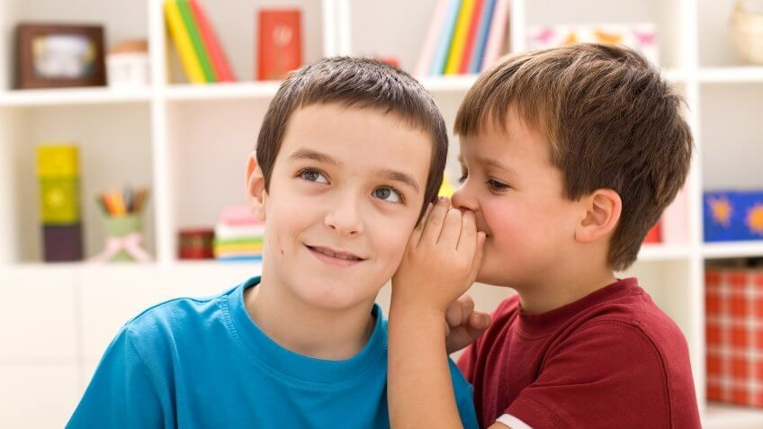 boy whispering into brother's ear