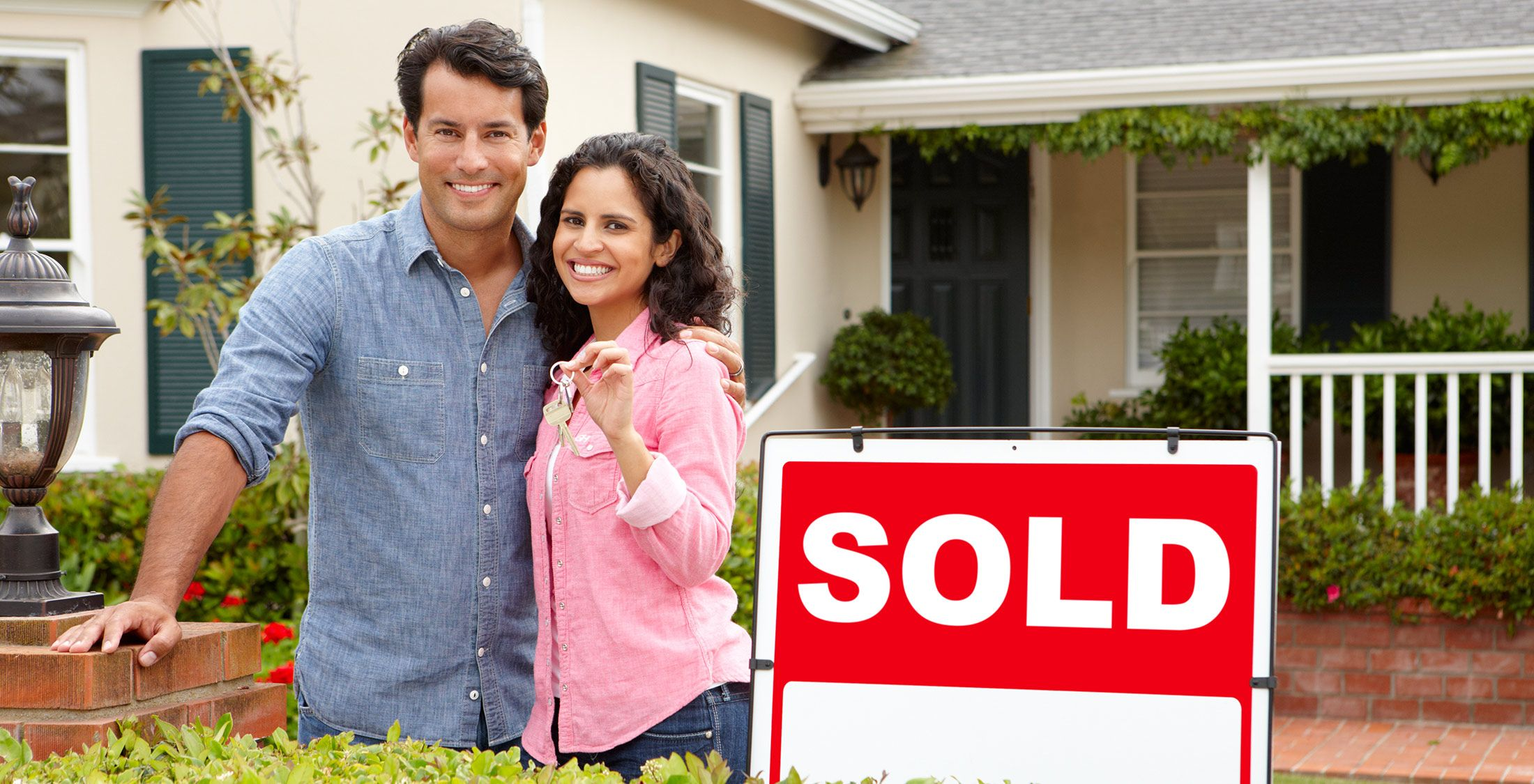 couple standing in front of sold house