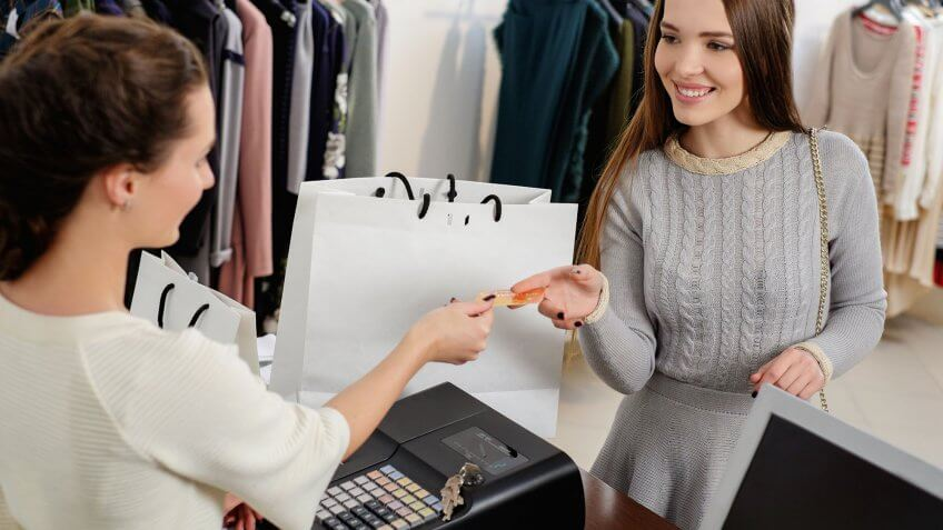 woman handing over card to clothing store clerk