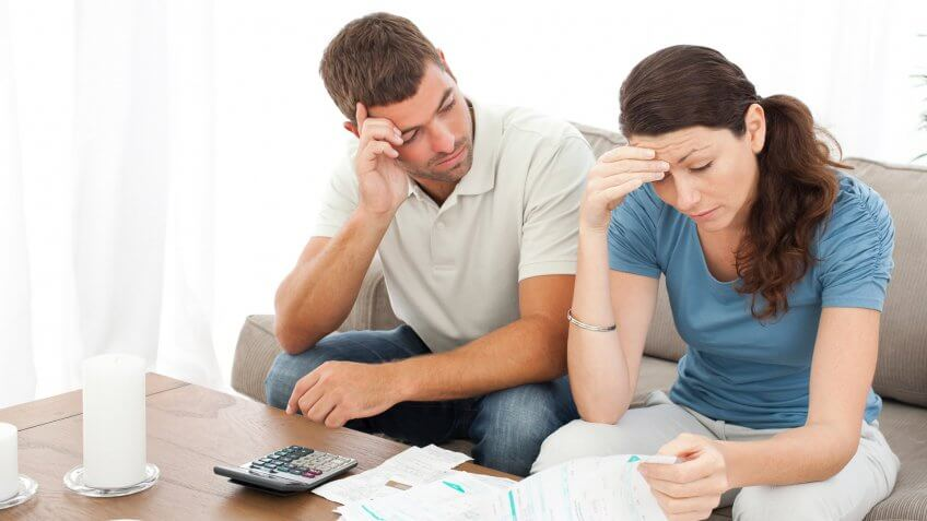 man and woman looking frustrated at documents