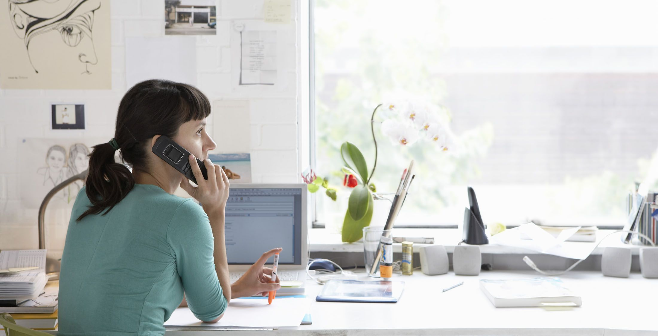 woman with computer talking on phone in office