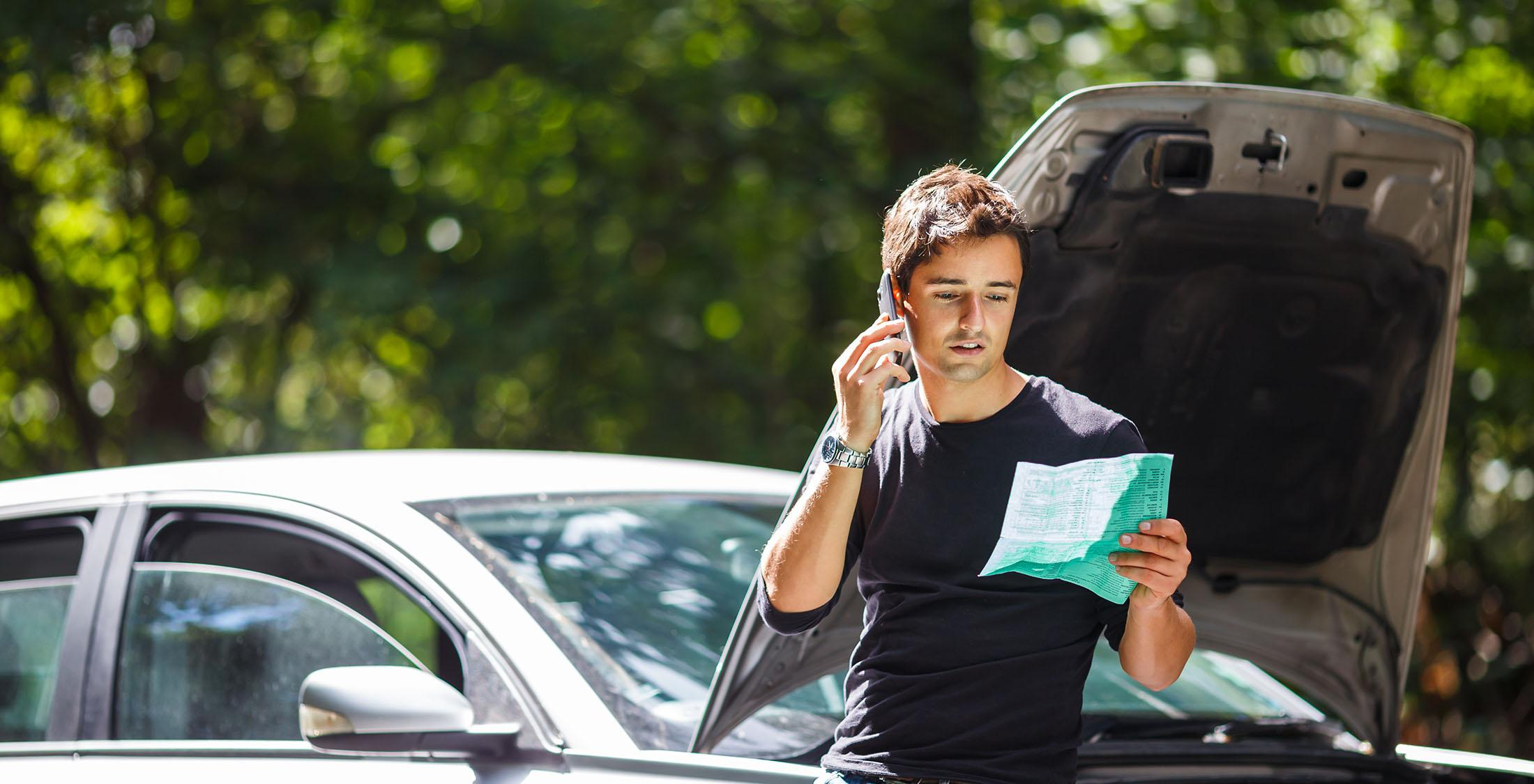 man on phone in front of car