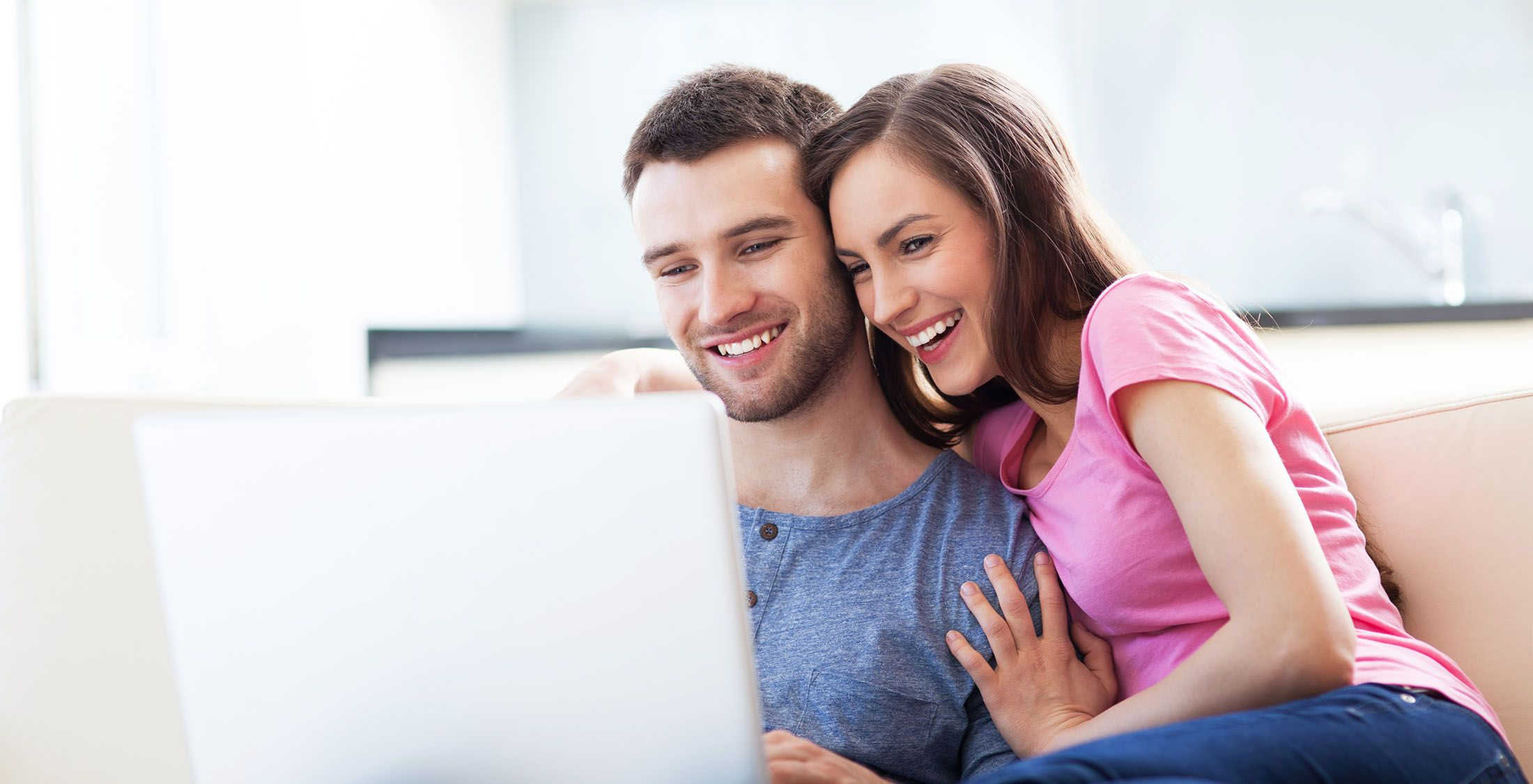 couple sitting on couch looking at computer