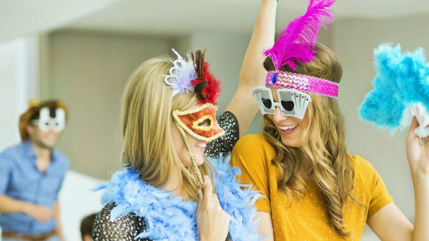 Women wearing decorative glasses and headpieces at party.