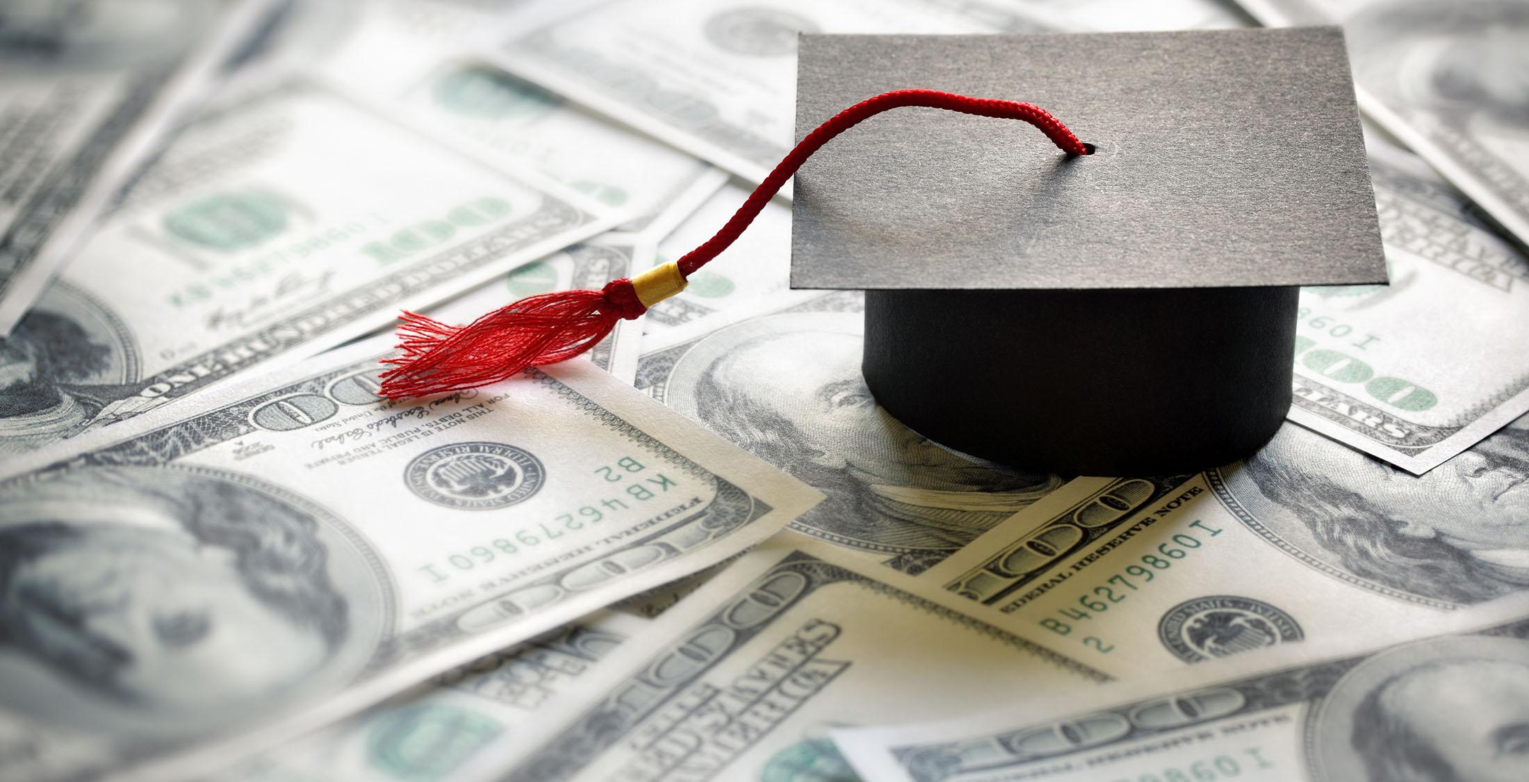graduate cap on top of one hundred dollar bills