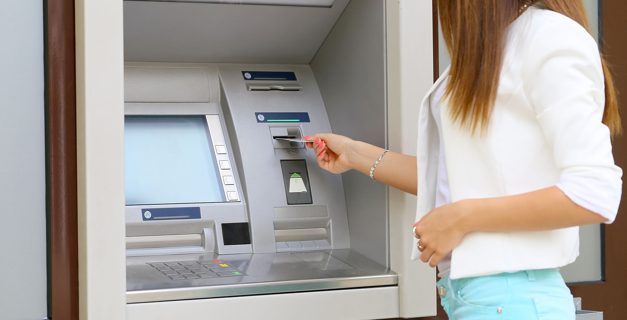 woman putting card into atm