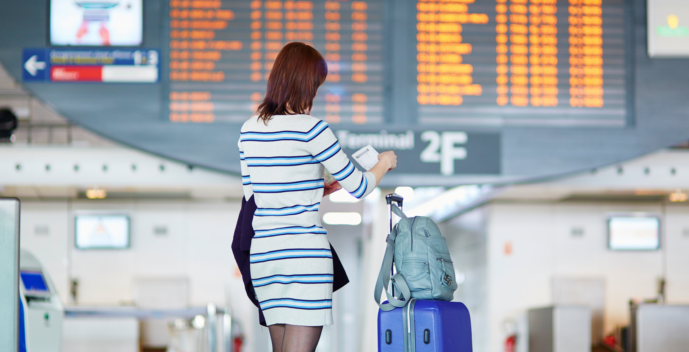 woman at airport in front of arrival departure board