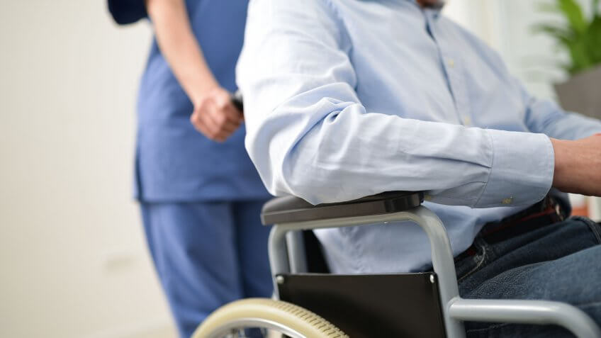 nurse pushing around man in wheelchair