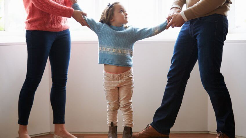 parents tugging daughter by arms