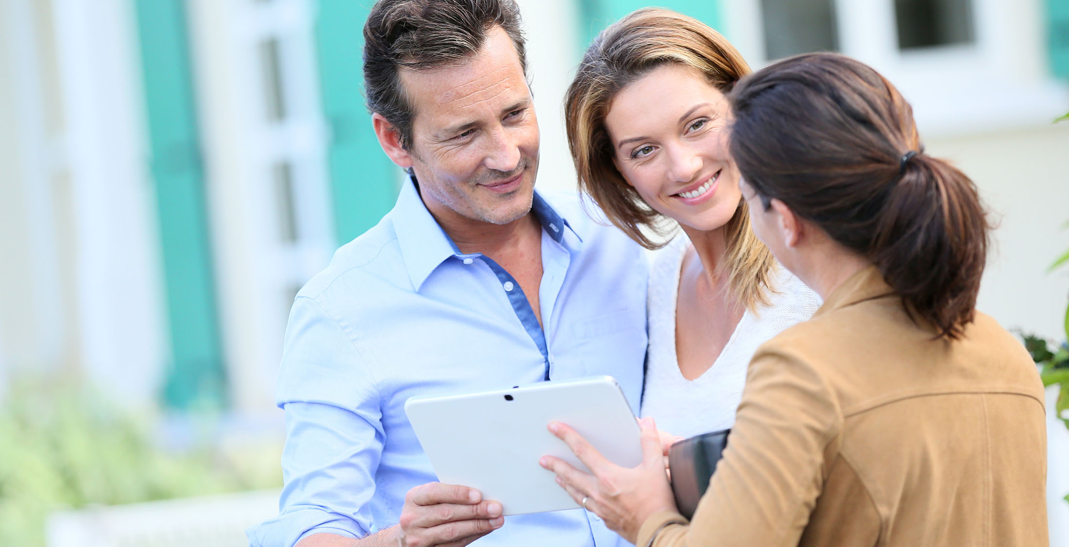 real estate agent showing couple something on tablet