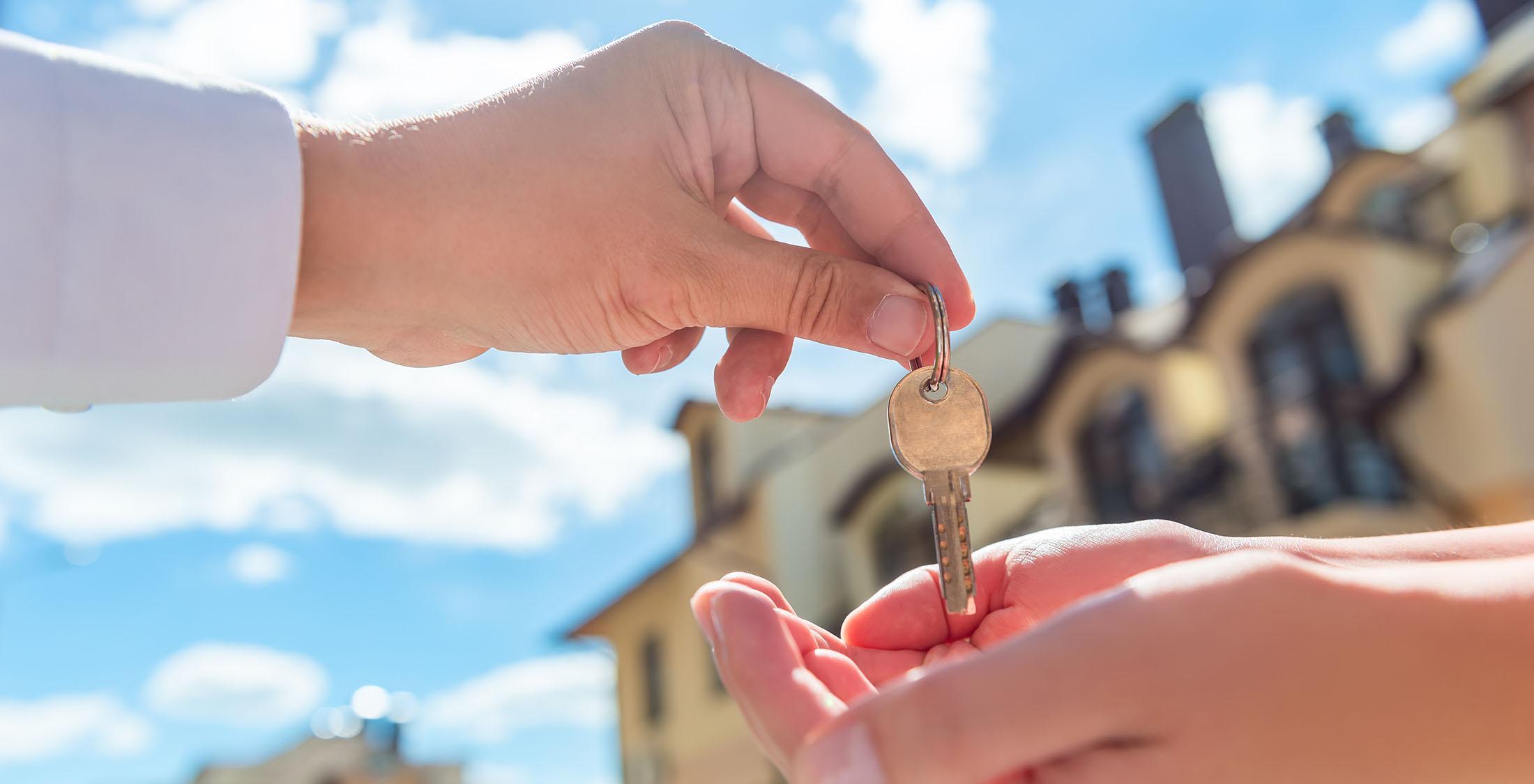 handing off keys in front of house