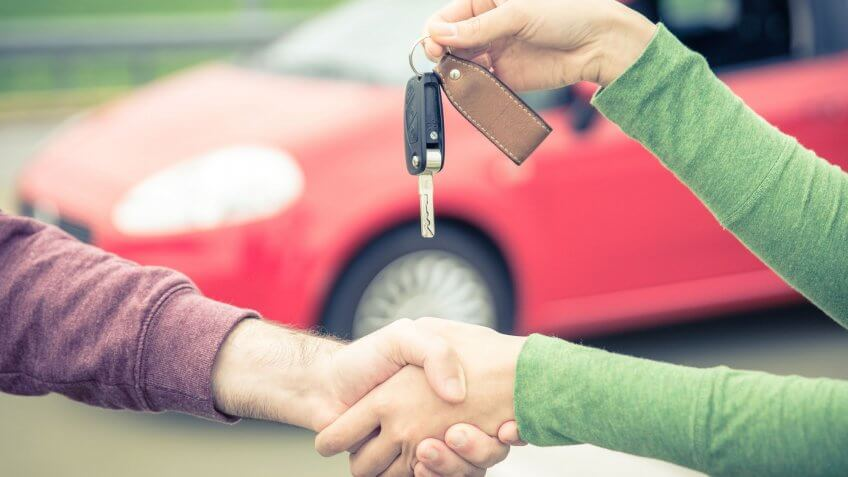 woman handing over car keys to man