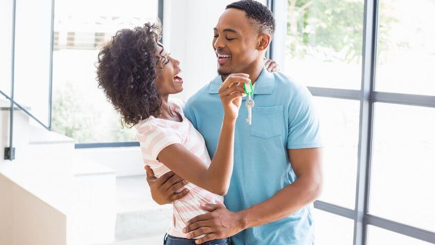 couple hugging holding keys