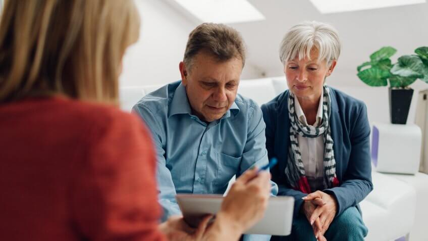 Mature Couple Meeting with Financial Advisor, selective focus to senior man and mature woman listening to financial advisor.