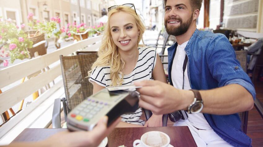 young couple paying for coffee with wireless credit card pay