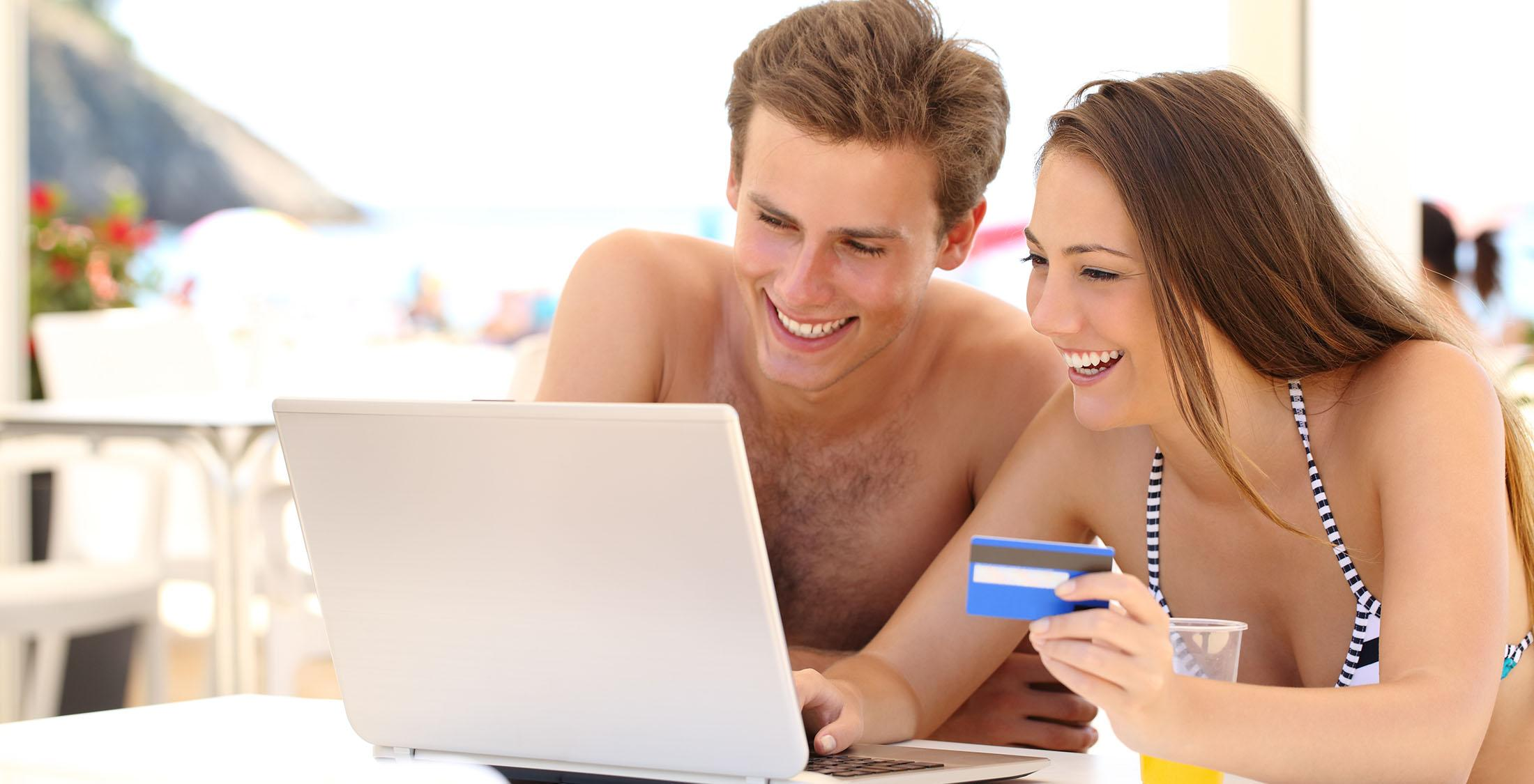 man and woman with credit card using laptop