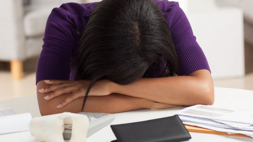 stressed woman with head down on desk