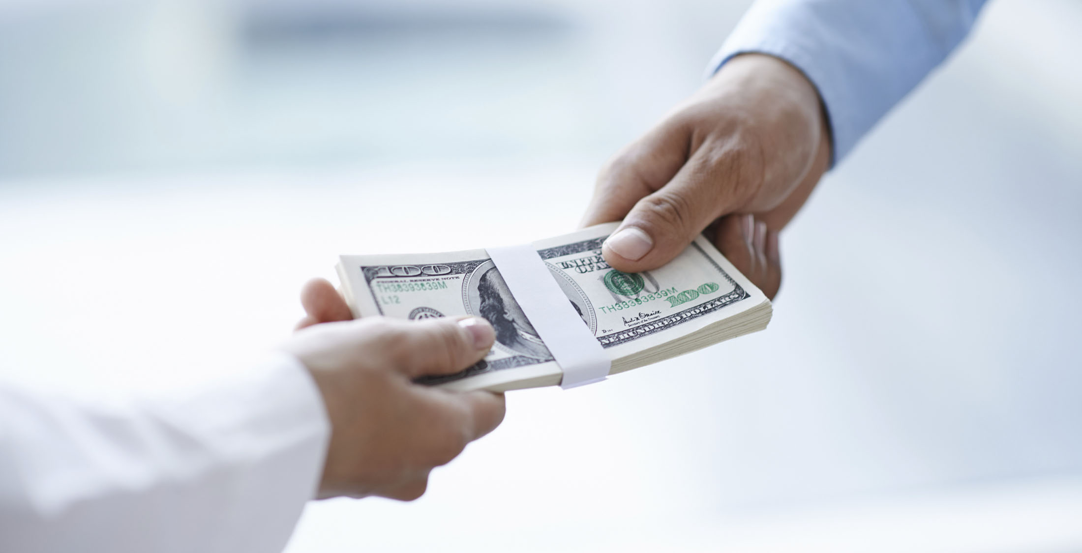 Hands of businessman giving money to his partner