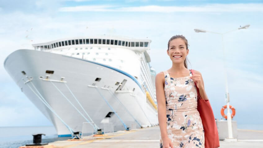 woman smiling on dock with cruise liner in background