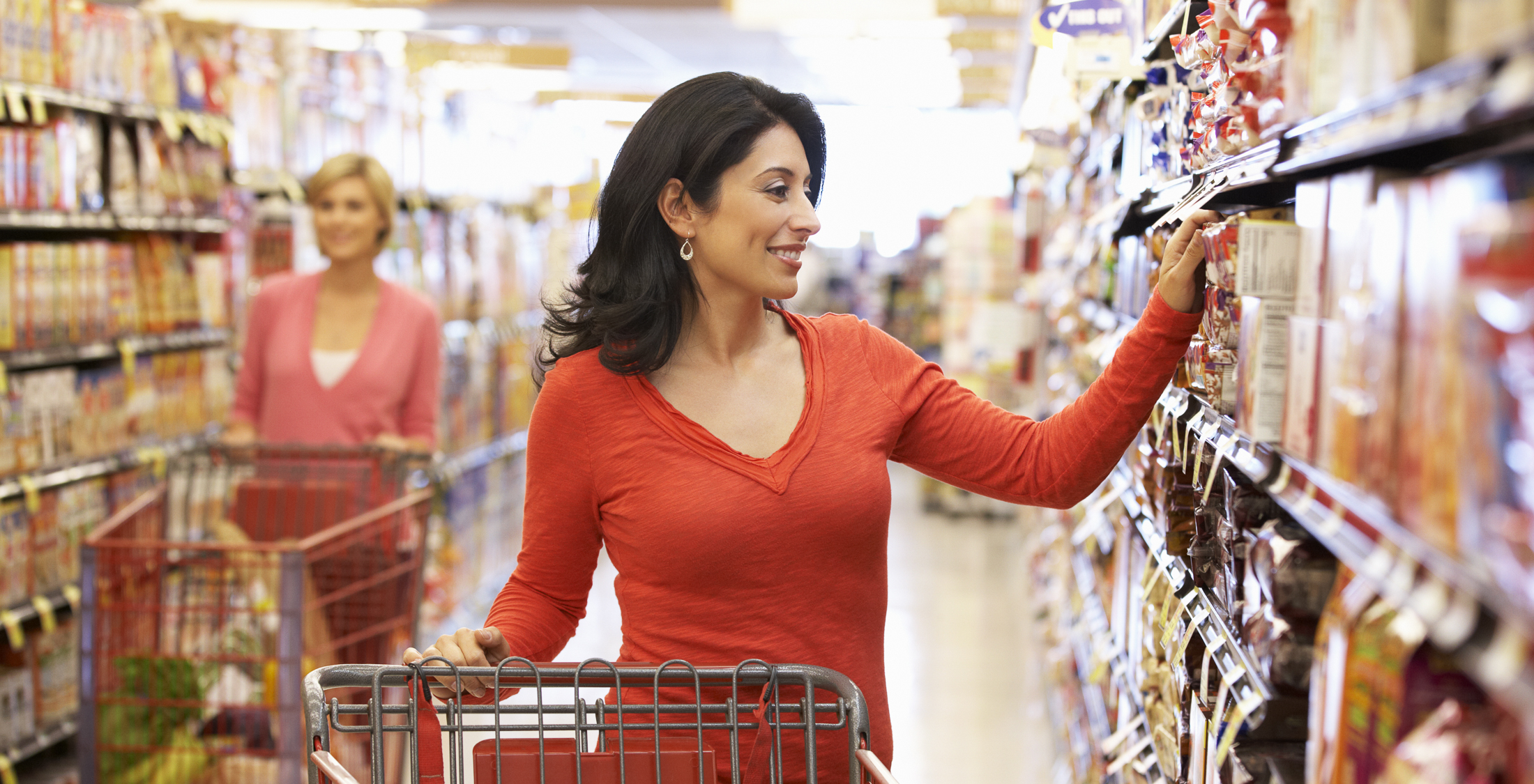 woman with grocery cart grabbing item from shelf