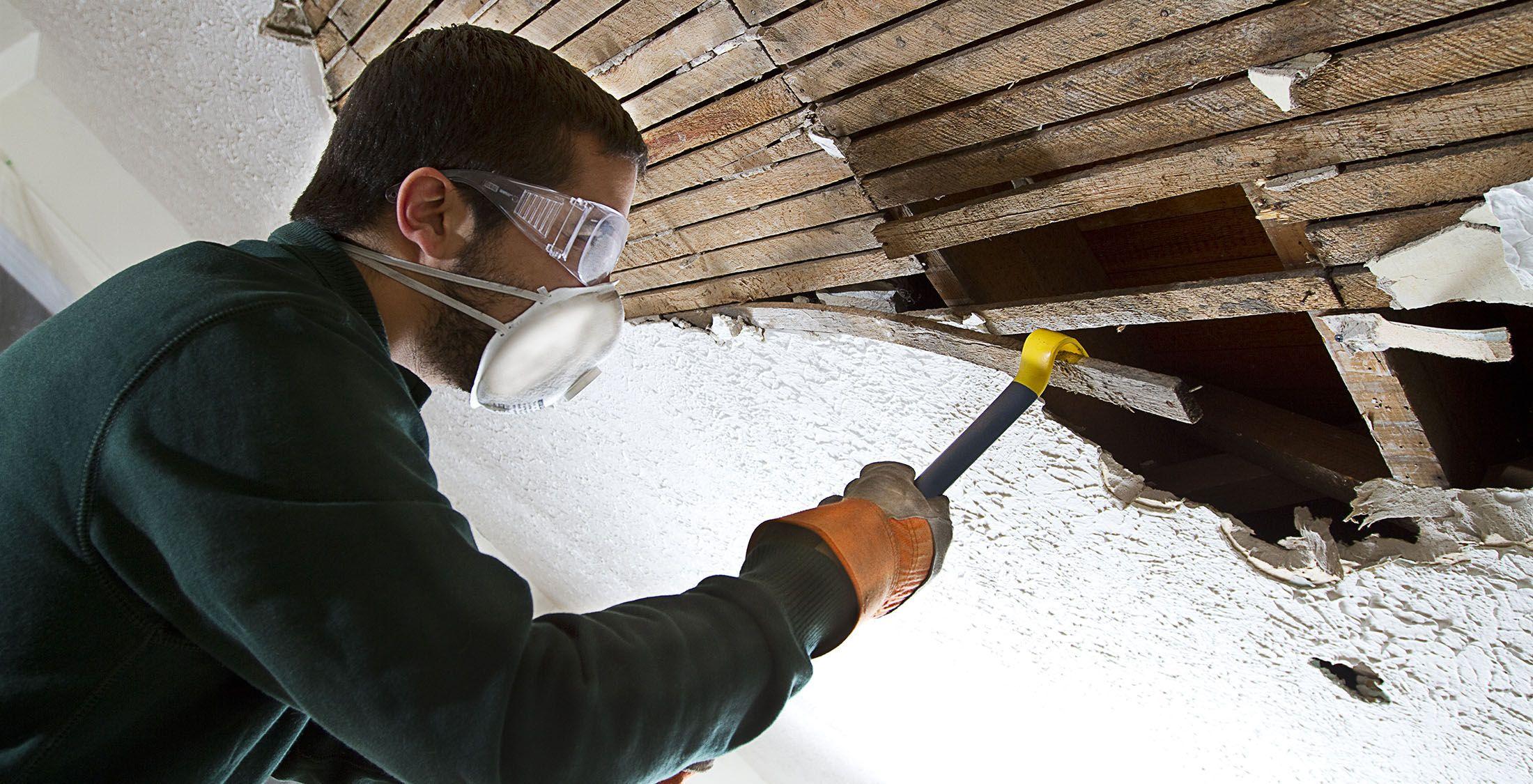 man taking apart wall with crowbar