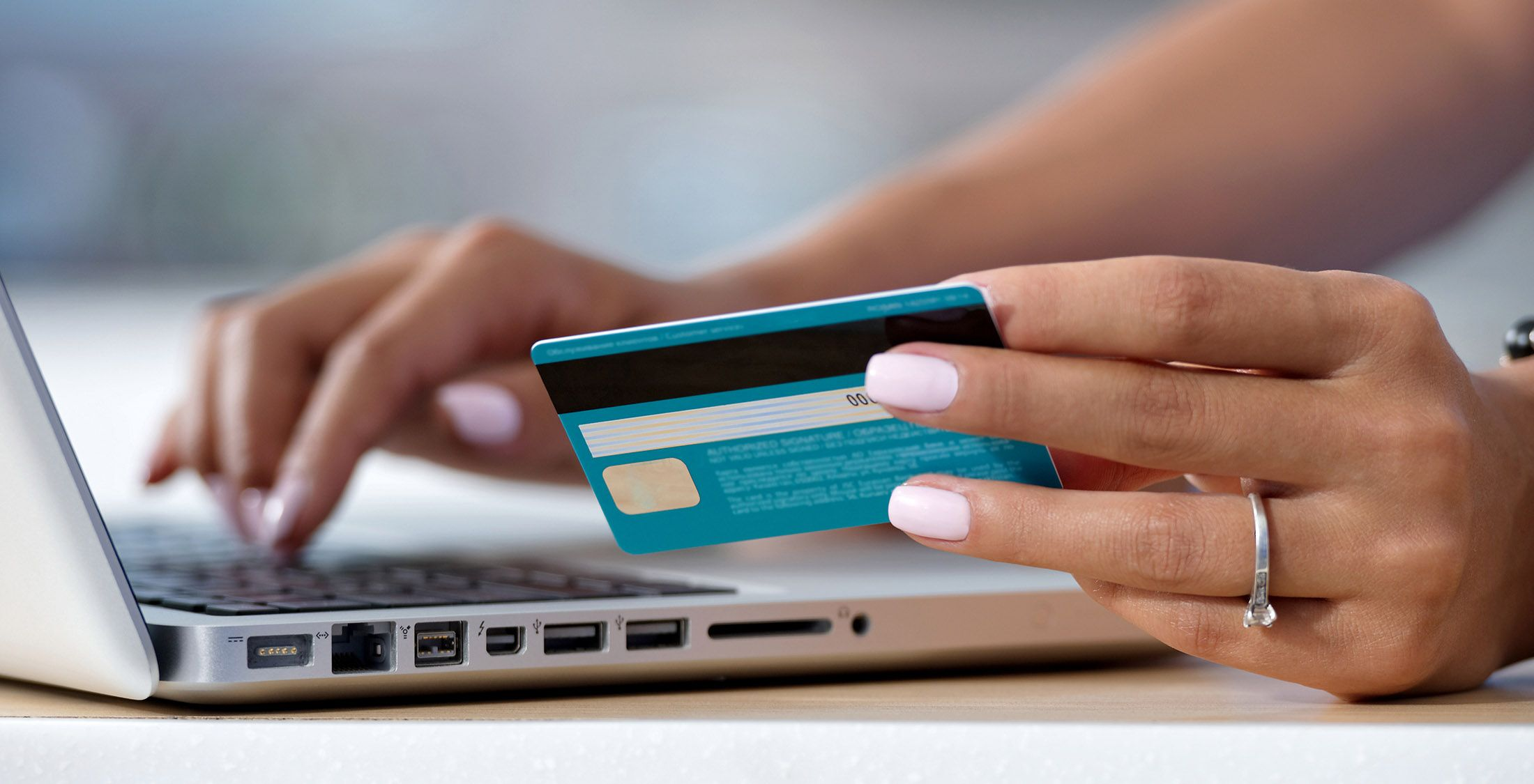 woman typing credit card info into laptop