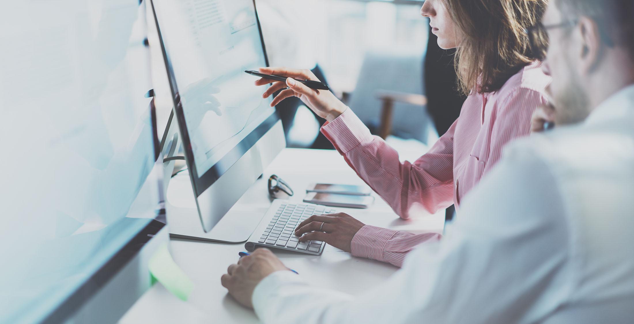 woman analyzing data on computer screen