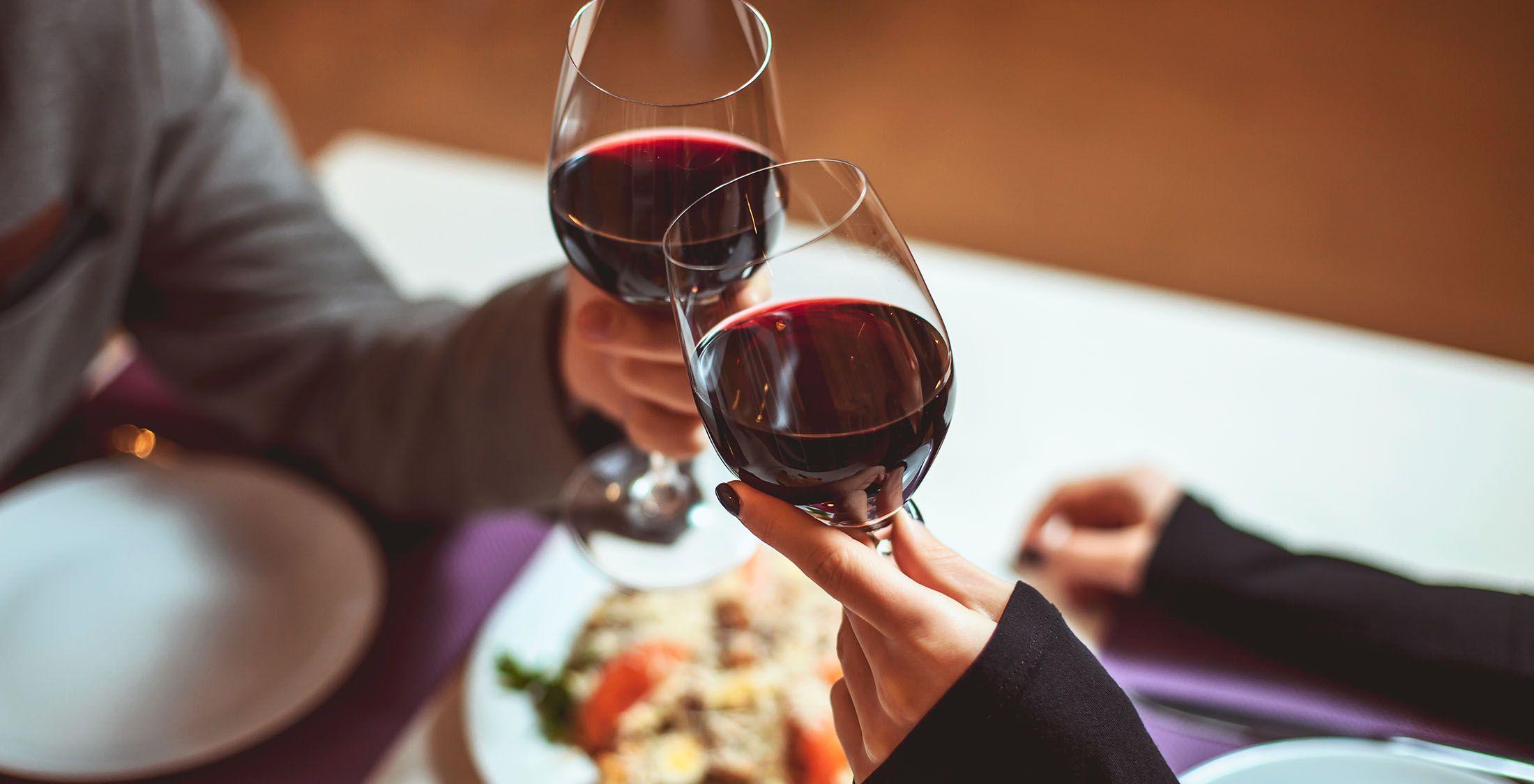 two people toasting wine glasses