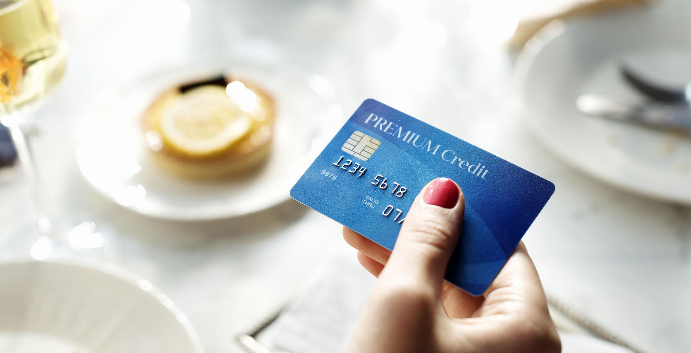 hand holding credit card on table