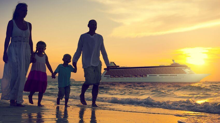 family walking hand-in-hand on beach at sunset