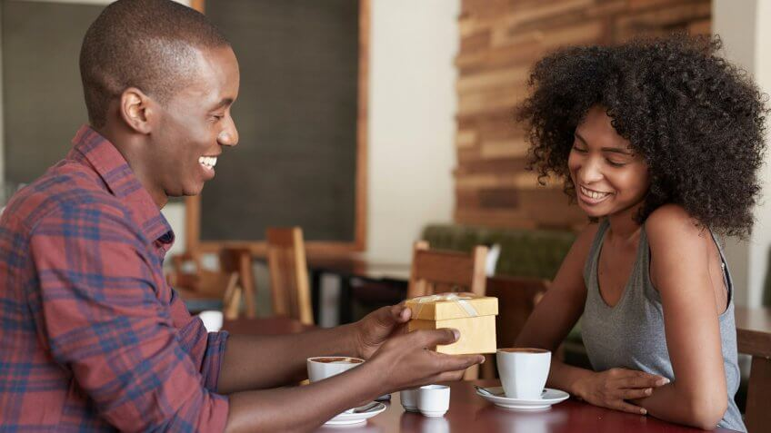 man giving a woman a gift at a coffee shop
