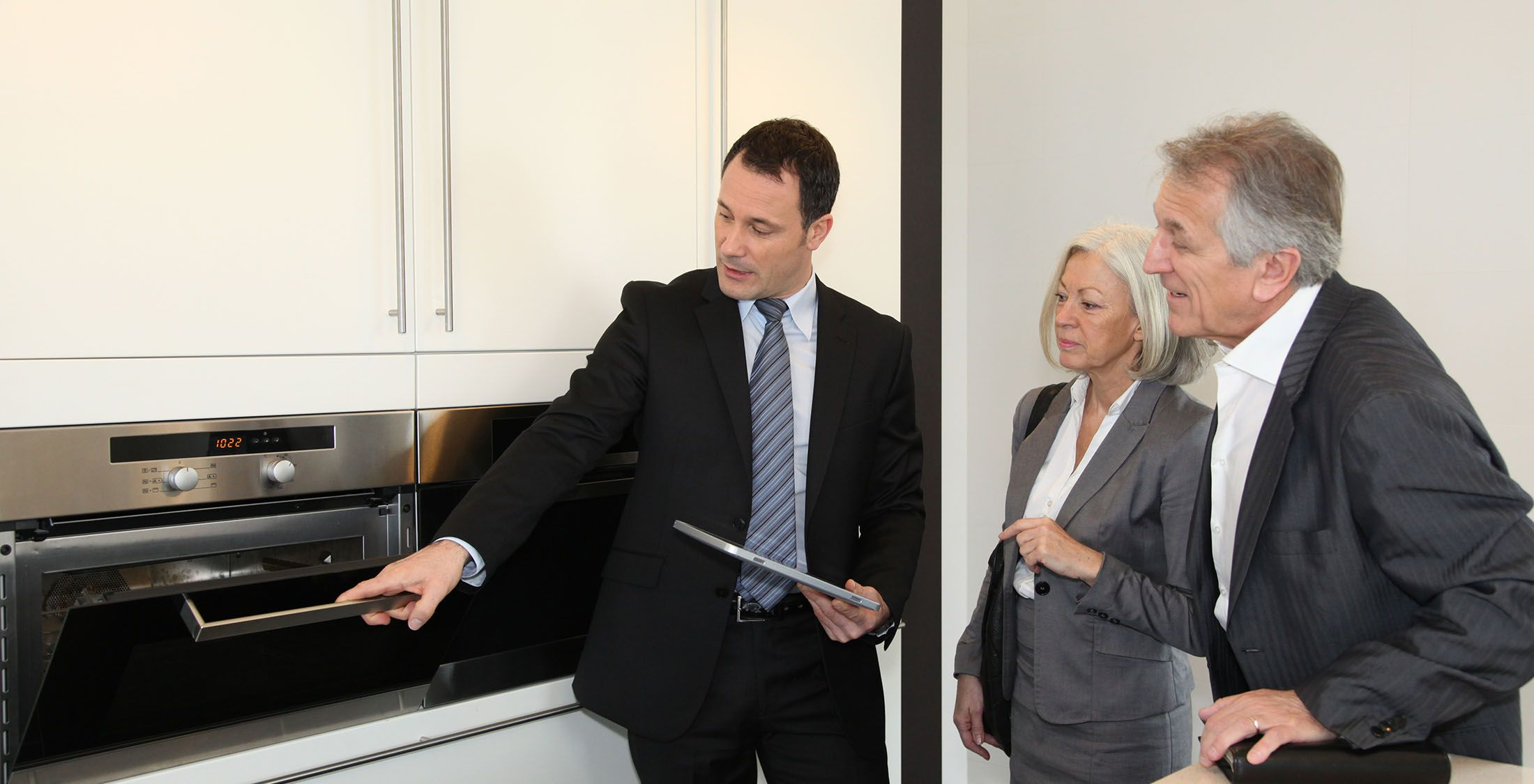 real estate agent showing elder couple an oven