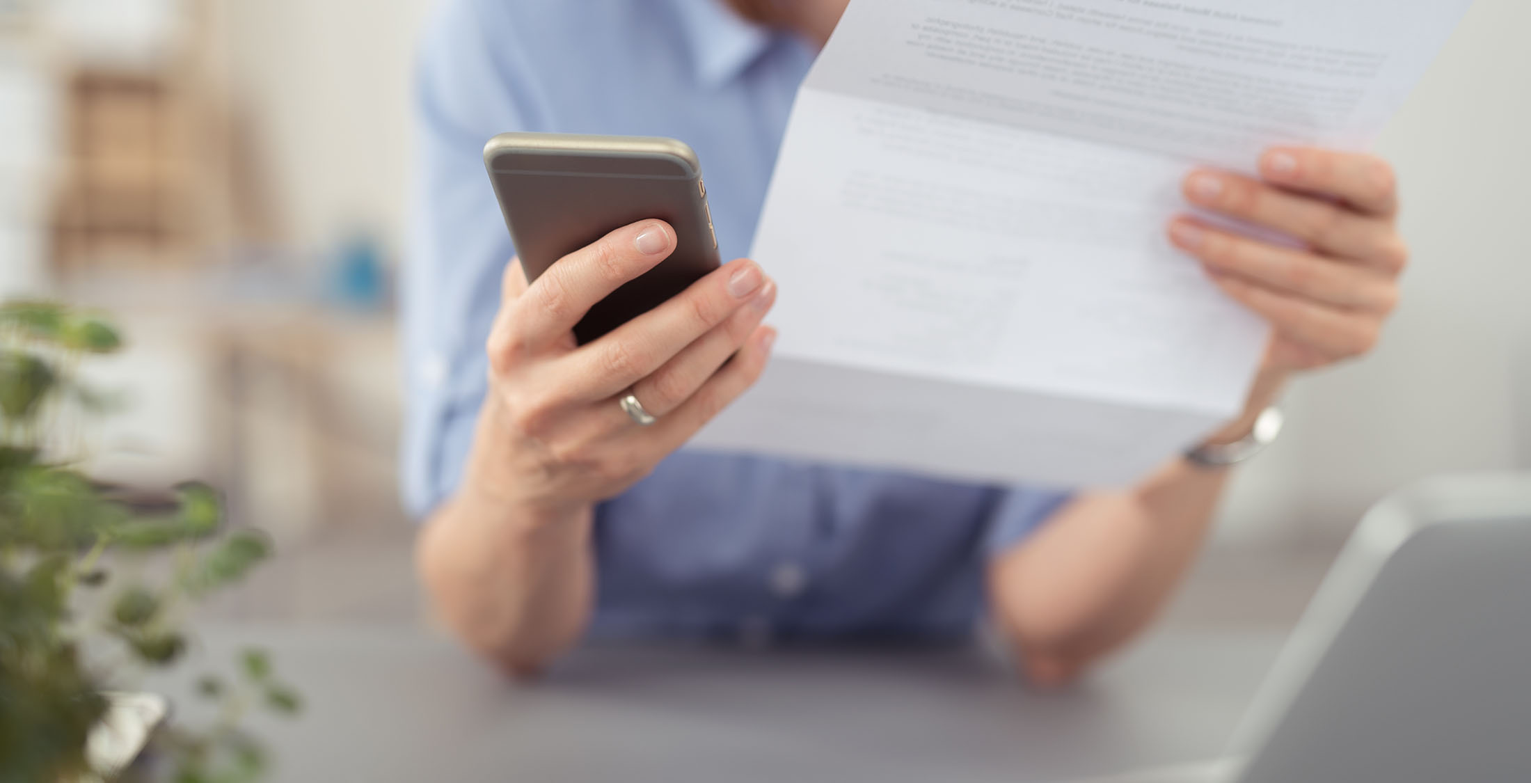 person holding phone and paper