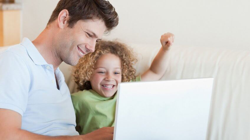 father and child looking at computer together