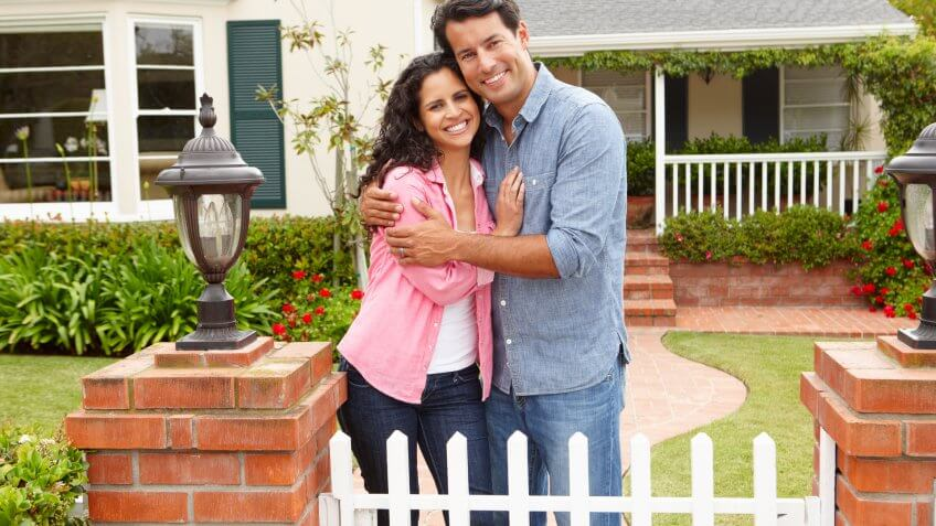 young couple smiling in front of their home