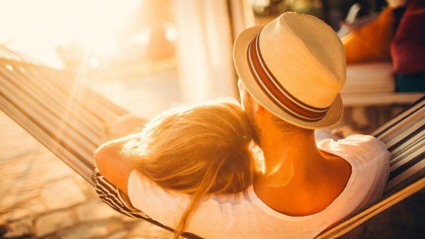 man and woman cuddling on a hammock outside