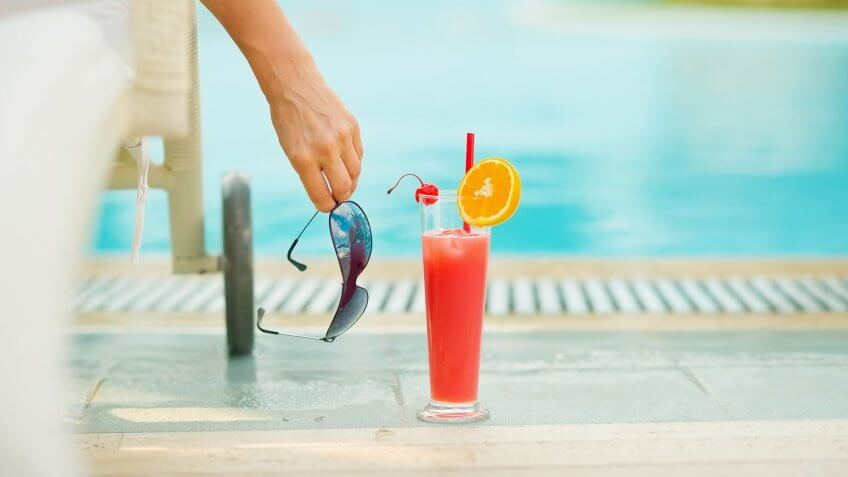 alcoholic drink by person's side at the pool