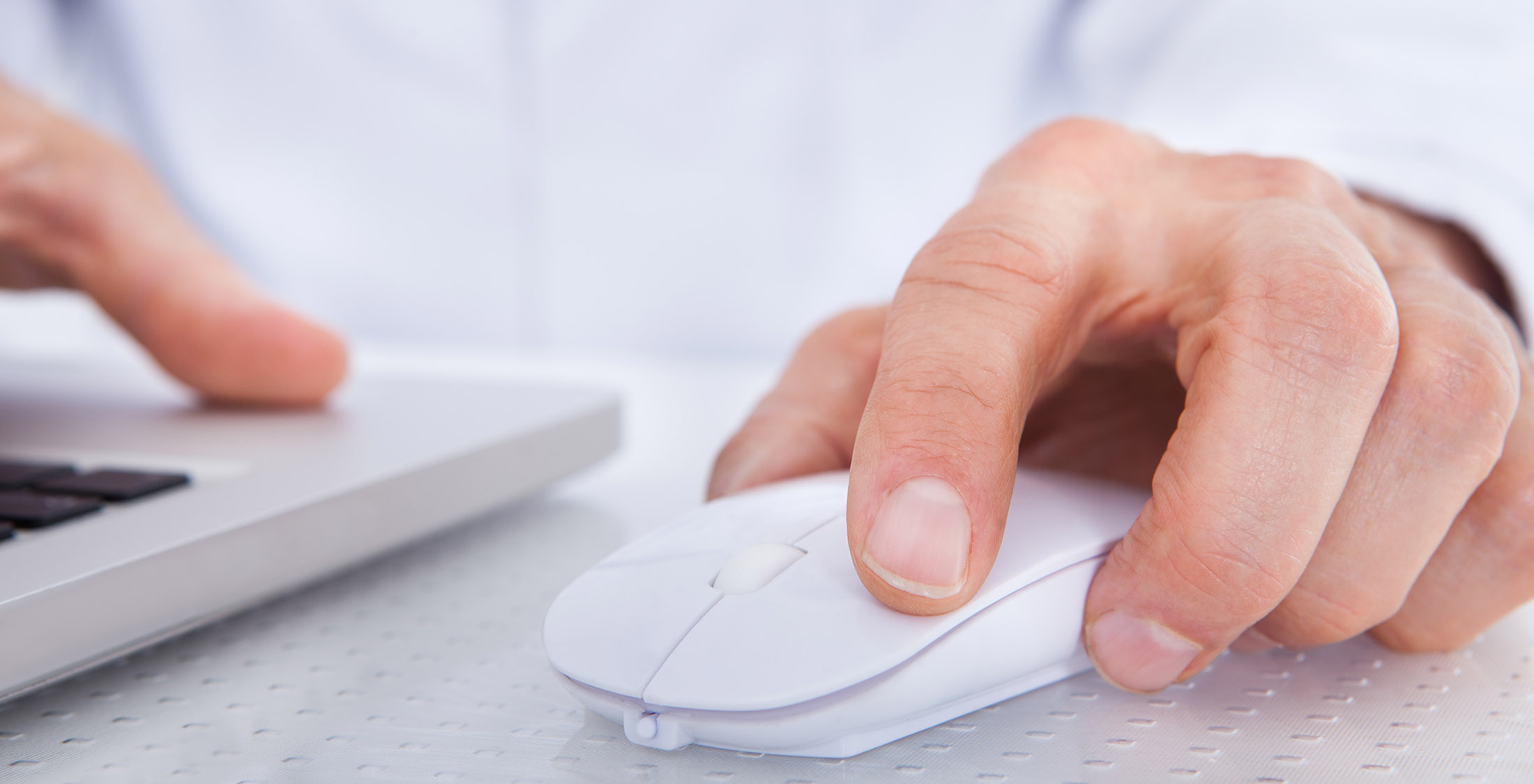 closeup of person's hand using computer mouse